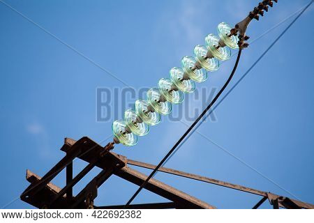 Glass Insulator For High Voltage Power Transmission Line. In The Frame There Is A Metal Tower, Wires