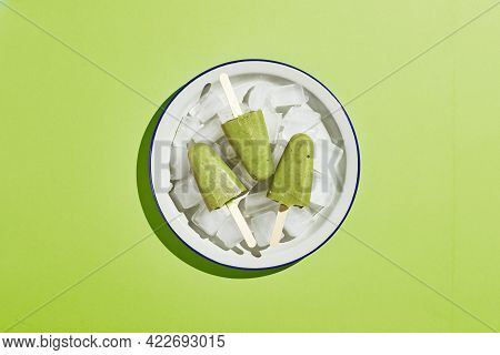 Frozen Homemade Pistachio Popsicle In Bowl Of Ice On Green Background. Refreshing Popsicle, Frozen G