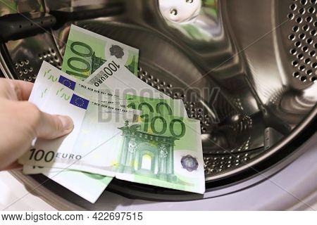 Money Is Put Into The Washing Machine, Close-up. Euro Banknotes In Washing Mashine Money Laundering.