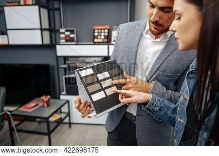 Salesman Shows Color Swatches To Lady Customer For New Kitchen Furniture