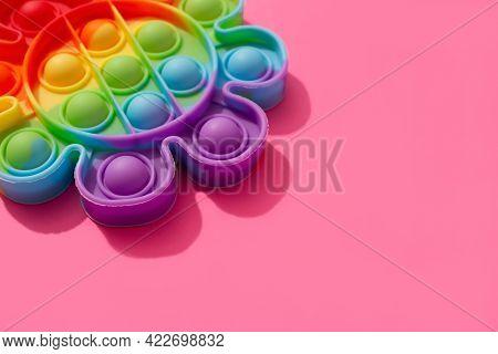 Close Up View Of Rainbow Pop It Fidget Toy On Pink Background With Copy Space. Push Bubble Fidget Se