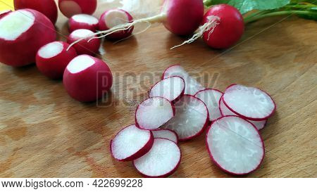 Ripe Clean Radish Roots Lie On A Cutting Board. Harvest Of Radish Close-up. Early Vegetables Are Rea