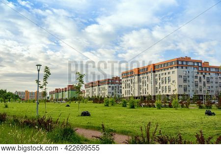 City Park On The Background Of Multi-storey Multi-colored Residential Buildings. There Are Black Sac