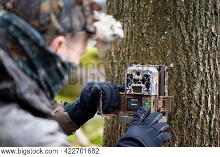 Wildlife Enthusiast Setting Up A Trail Camera On Tree And Operating Buttons