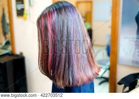 Coloring Several Strands Of Dark Hair Pink And Purple. Hairstyle In The Salon.