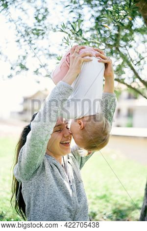 Smiling Mom Holding Her Little Girl Upside Down