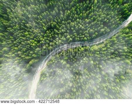 Aerial View Of Curved Country Road With Green Summer Fog Forest In Finland.