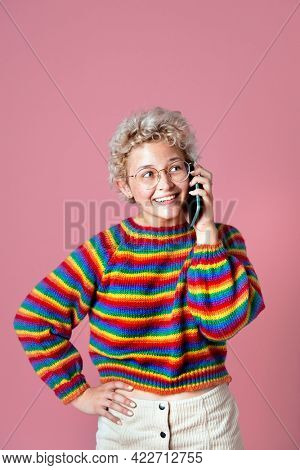 Cute cheerful girl in a rainbow sweater and a green beret talking on the phone