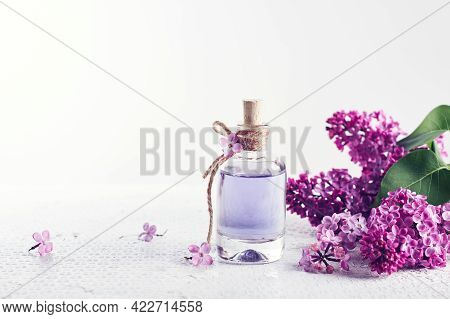 Perfume Bottle And Purple Lilac Flowers. Perfumery And Cosmetics Concept.