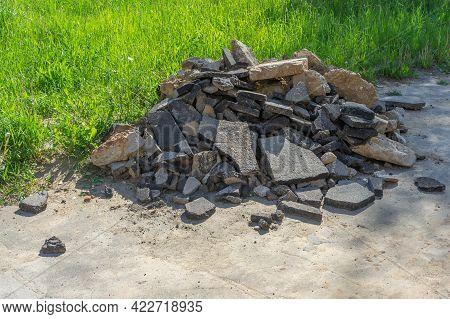 Chunks Of Dismantled Asphalt Piled Up On The Sidewalk. Construction Waste From Dismantling Stones