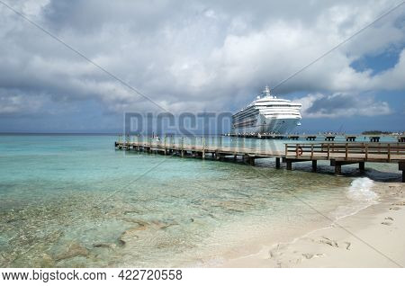 The View Of A Wooden Pier And A Large Cruise Ship That Arrived To Grand Turk Island (turks And Caico