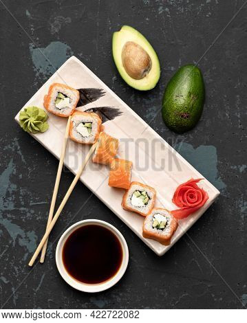 Flat Lay, Sushi Set On Black Background. Philadelphia Rolls With Salmon And Avocado Ready To Eat. He