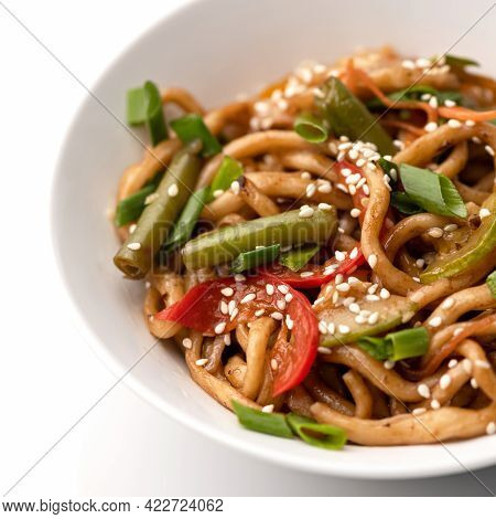 Close Up Of Spaghetti With Vegetables And Sesame Seeds. Vegetarian Noodles, Food Plate On White Back