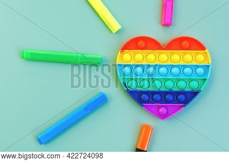 Top View Of Colorful Anti Stress Sensory Toy Pop It Rainbow Heart On Green Background Close Up. Crea