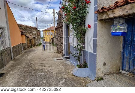 Woman Walking Down A Narrow Street In An Old Town With A Bird Cage On The Door Of A House. Avila.