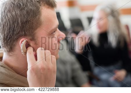 A Young Man Puts On A Hearing Aid. Portable Sound Amplifier For The Deaf And Hearing Impaired