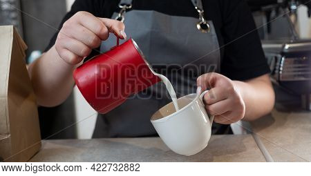 Close-up Of A Baristas Hands Pouring Milk Into A Cup Of Coffee. A Woman Makes A Latte Or Cappuccino