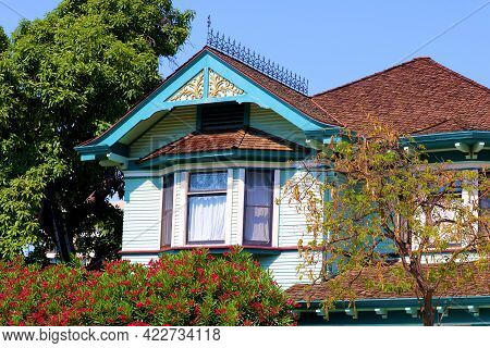 Historical Victorian Home Besides A Plant Hedge With Flower Blossoms Taken On A Suburban Street At A