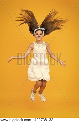 Salon That Brings Your Hair To The Next Level. Happy Child Jump Yellow Background. Small Girl With L