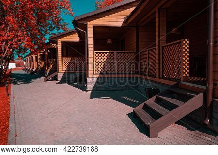 An Infrared Shot Of A Group Of Similar Wooden Houses Of A Youth Hostel Or A Campsite With Verandas A