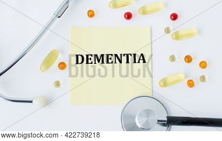 On White Background A Stethoscope, Pills And With Yellow Card With Text Dementia