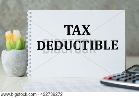 Text Tax Deductions On Notepad. Reduction On Taxes. Investment Savings. Money Returns