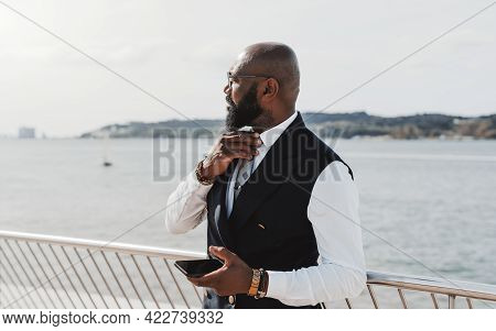An Elegant Bearded Bald Black Businessman In Glasses And Suit Is Straightening His Necktie While Sta
