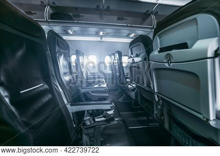 A Dark Aircraft Interior: The Row Of Modern Empty Thin Leather Seats With Armrests Down, Shallow Dep