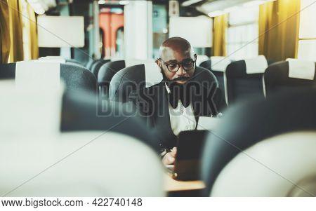 A Dapper Bearded Bald Black Man Entrepreneur In Eyeglasses Is Using His Laptop While Sitting Inside
