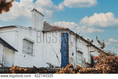 View Of A Beautiful Old Summer Cottage In European Suburbs On A Sunny Day With A Plaster Peeled Faca