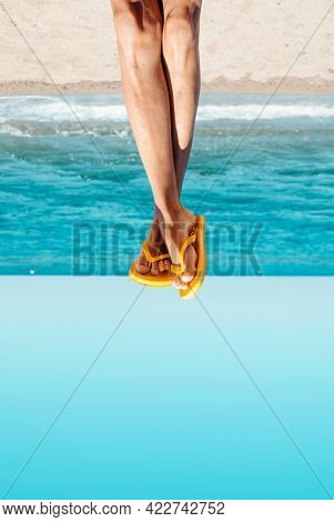 closeup of the legs of a young caucasian man on the beach wearing a pair of yellow flip-flops, upside-down,  with a blank space on the bottom