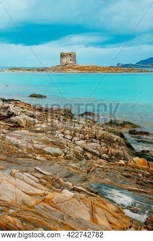 a view of some rock formations at the picturesque Spiaggia della Pelosa beach in Sardinia, Italy, with the Torre della Pelosa tower and the Isola Piana island in the background