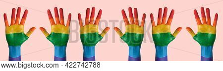 some pairs of raised hands painted as the rainbow flag against a pale pink background, in a panoramic format to use as web banner or header