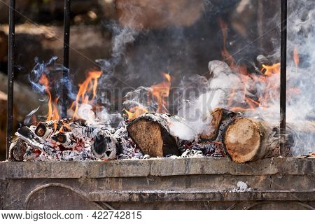 A Hearth With Burning Wood. The Logs Are Engulfed In Flames, Charred And Smoking. Selective Focus.
