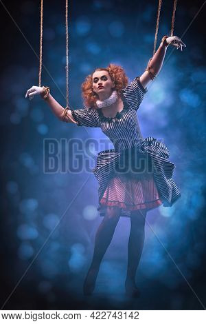 The actress plays a doll on strings at a performance in a puppet theater. Puppet theater and circus. Full length portrait in vintage style.