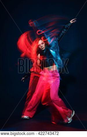 Contemporary dances. Professional hip hop dancer girl dancing at studio in neon light.