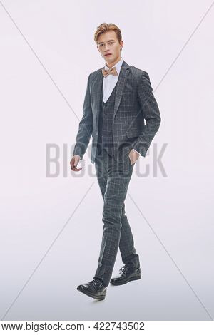 Men's beauty, fashion. Full length portrait of a good looking handsome blond man wearing elegant classic suit and a bow-tie on a white background.