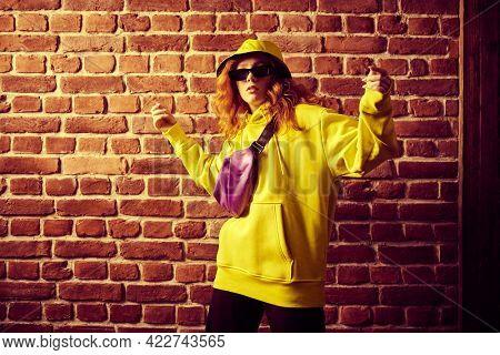 Modern young hip hop dancer girl in yellow hoodie dancing contemporary urban street dance. Brick wall background.