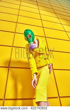 Fashion of the future. Full length portrait of a woman in elegant yellow suit and green gas mask posing by a yellow industrial wall. Environmental disaster, apocalypse.