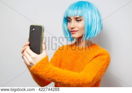 Studio Portrait Of Young Pretty Girl, Smiling And Taking Selfie Photo By Smartphone On Background Of