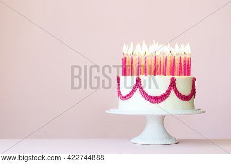 Birthday cake with lots of pink birthday candles on a pink background