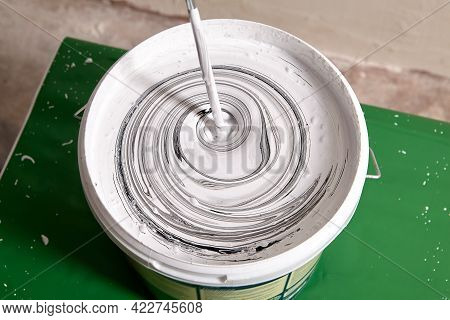 Adding Black Pigment To White Wall Paint For Mixing In Bucket Using An Electric Mixer Until Gray Col