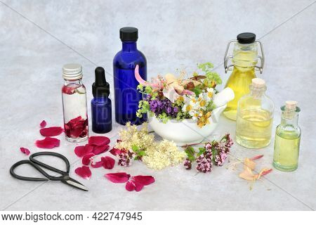 Summer herb and flower selection for preparing aromatherapy essential oils with oil bottles and flowers in a mortar with pestle and loose. Herbal plant medicine health care concept.