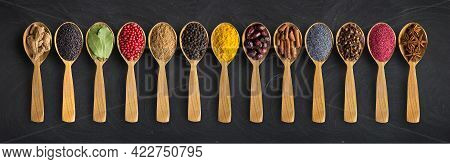 Spices Collection In Wooden Spoons On  Black Table. Spices For Website Headers  Or Packaging Design