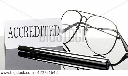 Text Accredited On Paper On Light Background With Pen And Glasses. Business