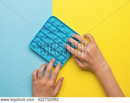 A Girl Plays A Popular Pop It Toy On A Yellow And Blue Background. A Popular Anti-stress Product.