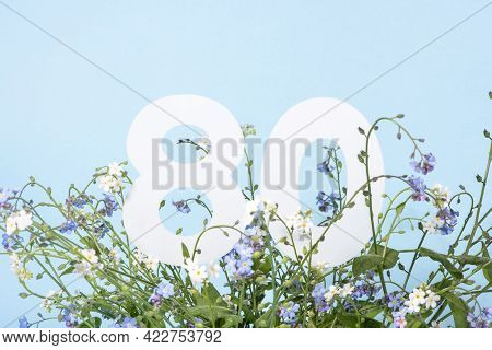 Number Eighty Among Blue Forget-me-not Flowers.  Birthday, Anniversary, Jubilee Concept. For Invitat