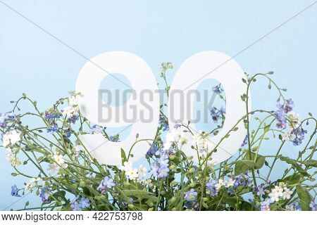 Number Ninety Among Blue Forget-me-not Flowers.  Birthday, Anniversary, Jubilee Concept. For Invitat