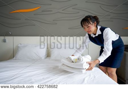 Young Hotel Maid With A Smile Putting Set Of Towel With White Flower On The Bed. Staff In Blue Unifo