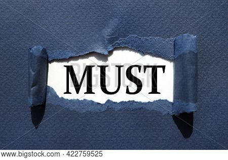 Must. Text On Torn Cardboard. Black Letters On White Paper